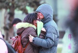 """一对情侣入场前拥抱亲吻,互相鼓励。2013年1月5日,全国180万考生走进考场,参加""""史上最严""""的硕士研究生招生考试。(本报记者张学军1月5日摄于中国青年政治学院考点)"""