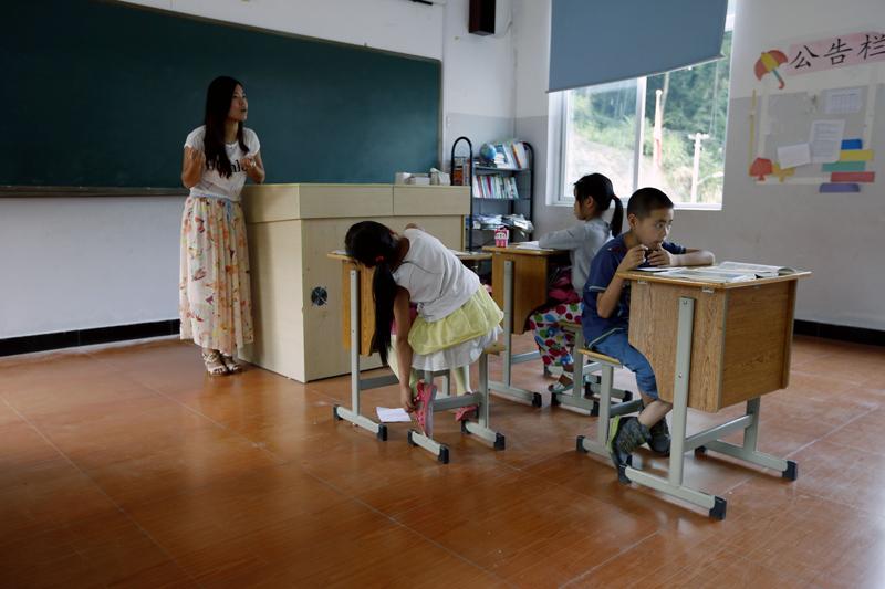 教室里,邵老师在认真给三年级学生上语文课。 由于山区蚊子多,影响了孩子上课专注。 图片由cfp授权使用,严禁转载