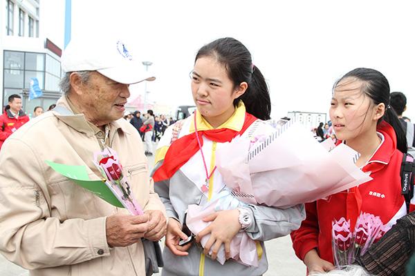 和平里第四小学学生偶遇曾7出征南极的79岁的平爷爷,向他献花并致敬(晓晓 摄)