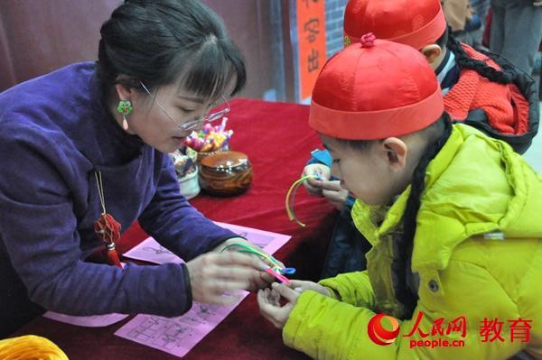 老师教小男孩编中国结。郭凯奇/摄。