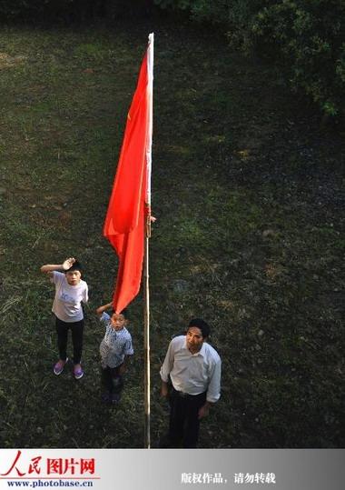 陈严贞老师带着何国香(右)和何国华(中)在升旗仪式上向国旗敬礼图片