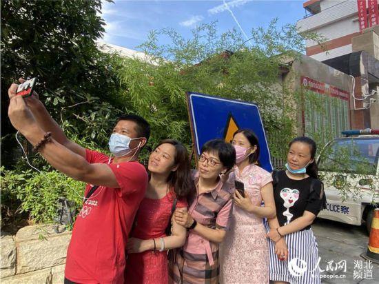 湖北省水果湖高级中学考点,家长为学生送考。人民网 肖璐欣摄