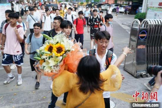 資料圖:6月8日,廣西南寧第二十九中學考點外,考生家長捧著花與考生擁抱。陳冠言 攝